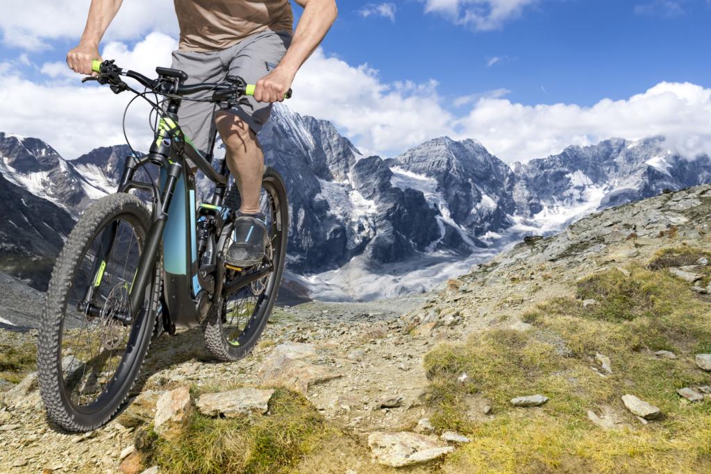 Ein Pedelec-Fahrer steht auf einem Berg